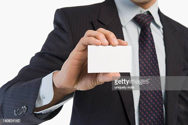 Mid section view of a businessman showing a blank business card