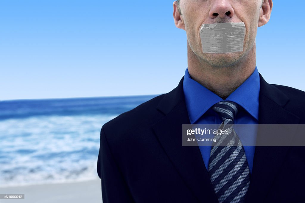 Mid Section View of a Businessman With Duct Tape Covering His Mouth Standing on a Beach by the Ocean : Stock Photo