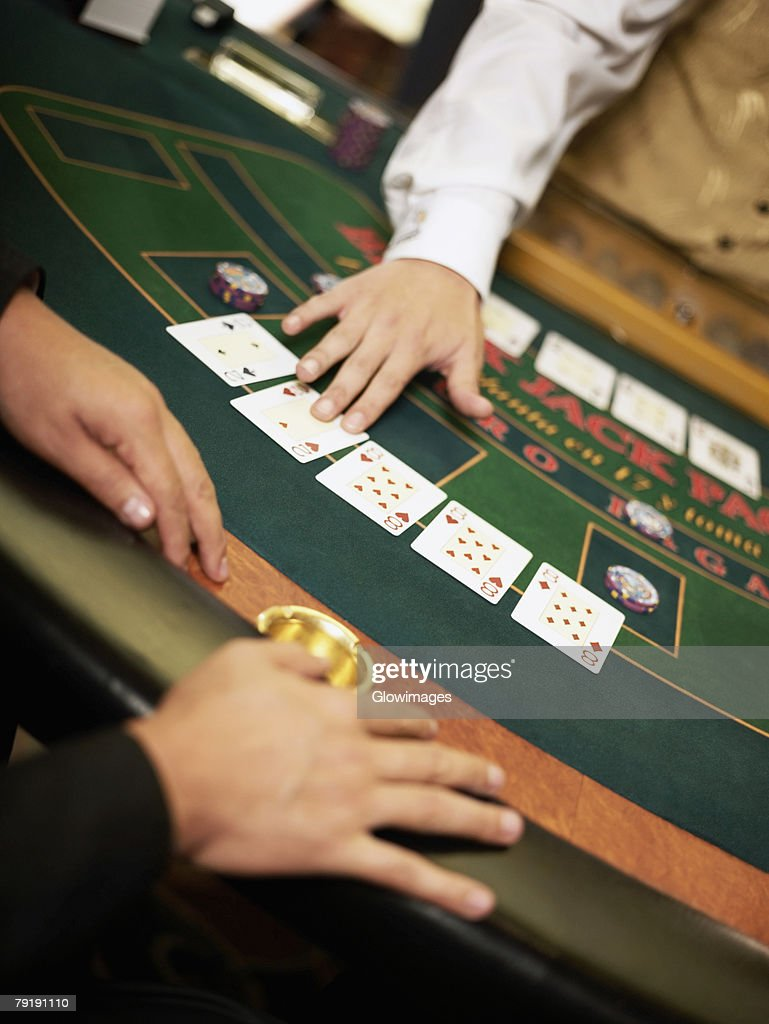 Mid section view of a casino worker dealing with playing cards on a gambling table : Foto de stock