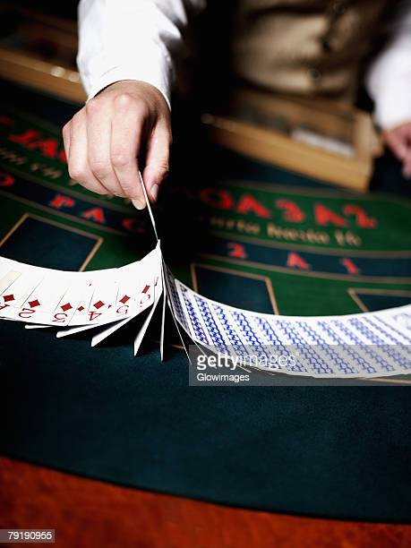 Mid section view of a casino worker's hand dealing with playing cards on a gambling table