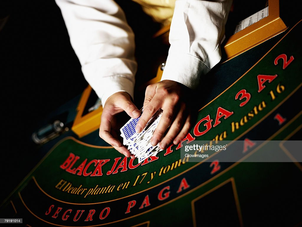 Mid section view of a casino worker's hand shuffling playing cards on a gambling table : Stock Photo