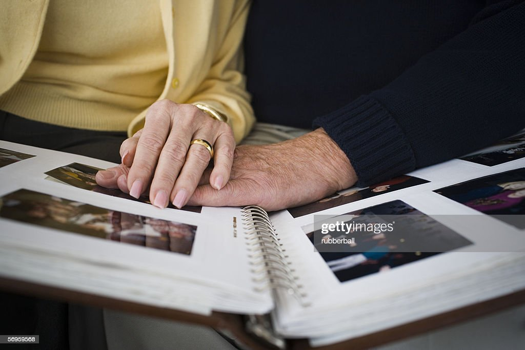 Mid section view of a couple looking at a photo album : Stock Photo