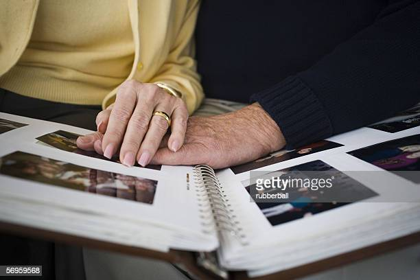 Mid section view of a couple looking at a photo album