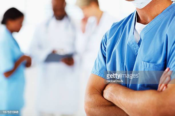 Mid section view of a doctor with hands folded