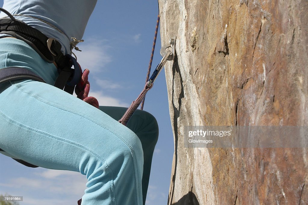 Mid section view of a female rock climber climbing a rock face : Foto de stock