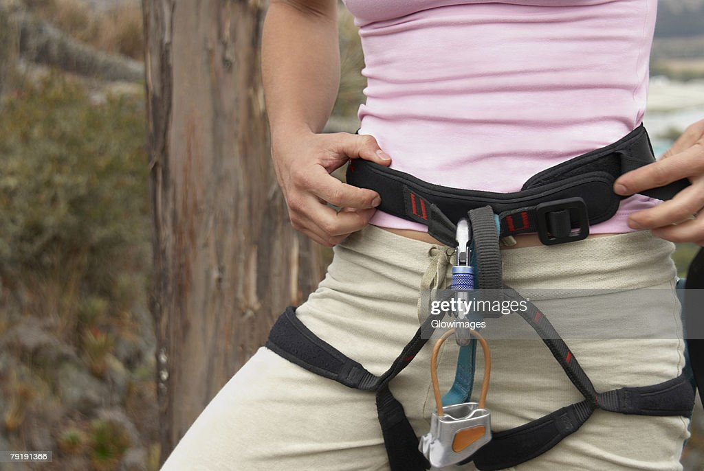 Mid section view of a female rock climber wearing harness : Foto de stock