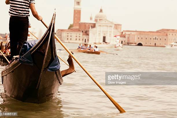 Mid section view of a gondolier sailing a gondola in a canal, Venice, Veneto, Italy