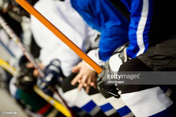 Mid section view of a group of ice hockey players holding ice hockey sticks