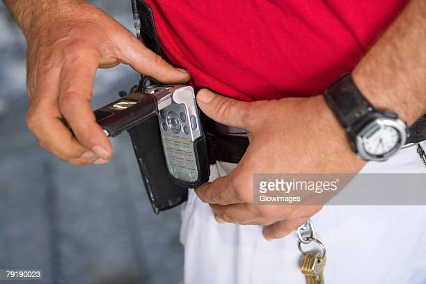 Mid section view of a man fastening a mobile phone on his belt