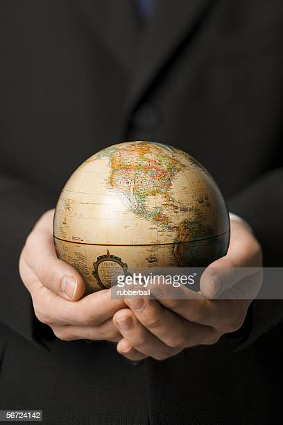 mid section view of a man holding a globe - world at your fingertips stock pictures, royalty-free photos & images
