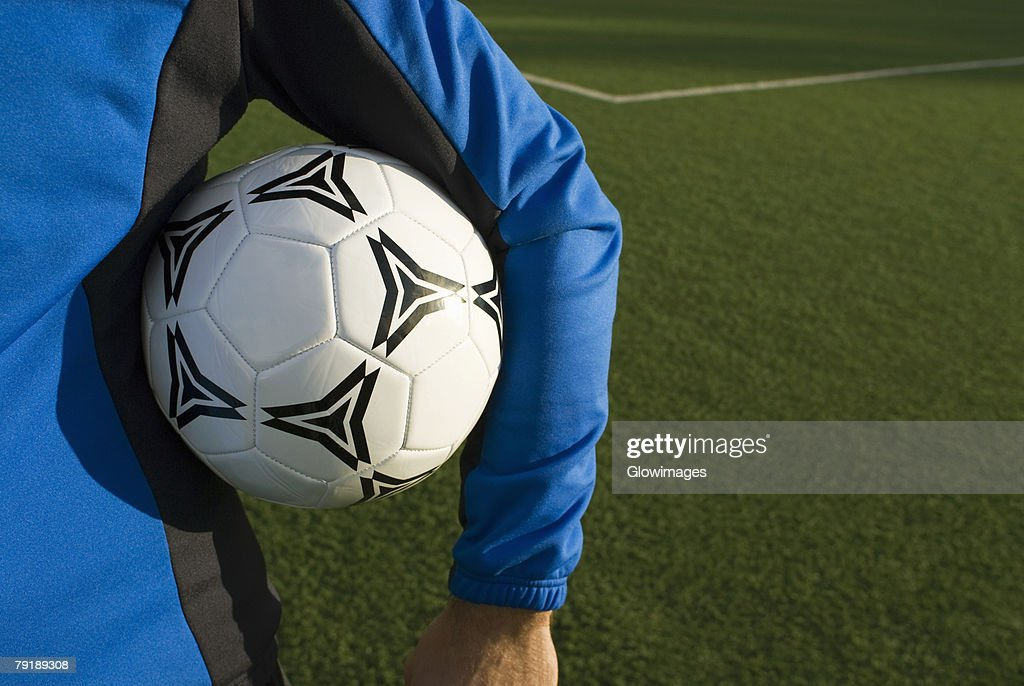 Mid section view of a man holding a soccer ball under his arm : Foto de stock