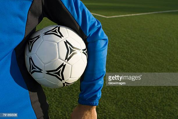 mid section view of a man holding a soccer ball under his arm - mid section stock photos and pictures