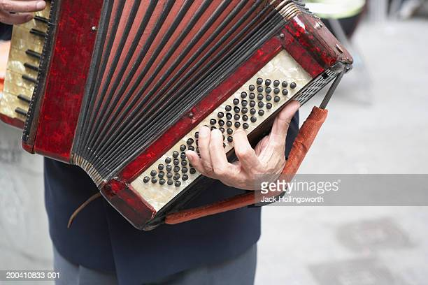 Mid section view of a man holding an accordion
