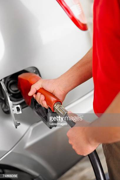 Mid section view of a man refueling a car