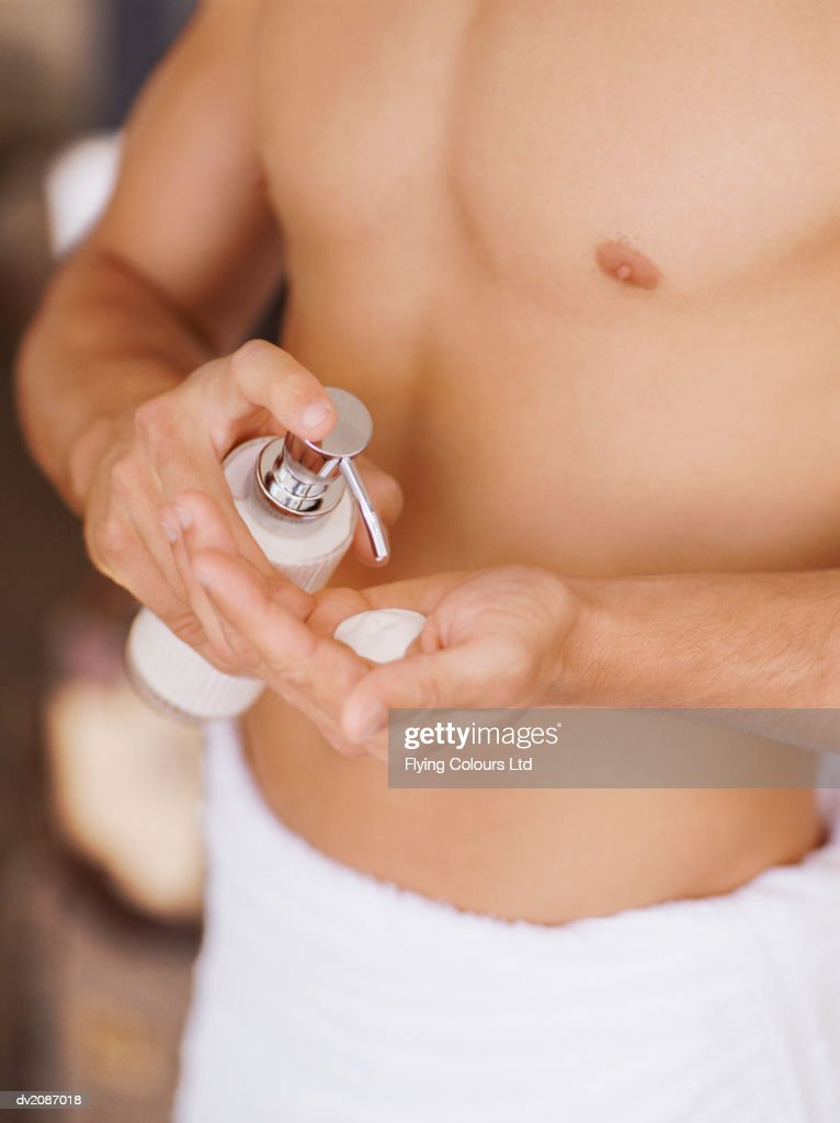 Mid Section View of a Man Wearing a Towel Putting Moisturizer Into His Hand : Stock Photo