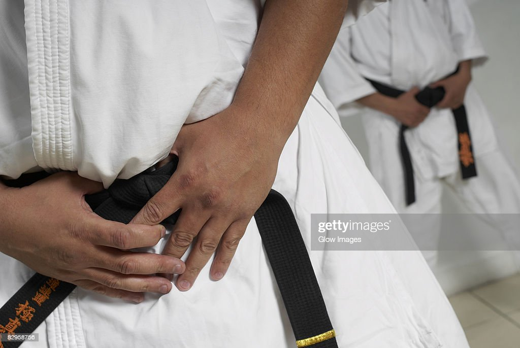 Mid section view of a man wearing karate uniform : Stock Photo