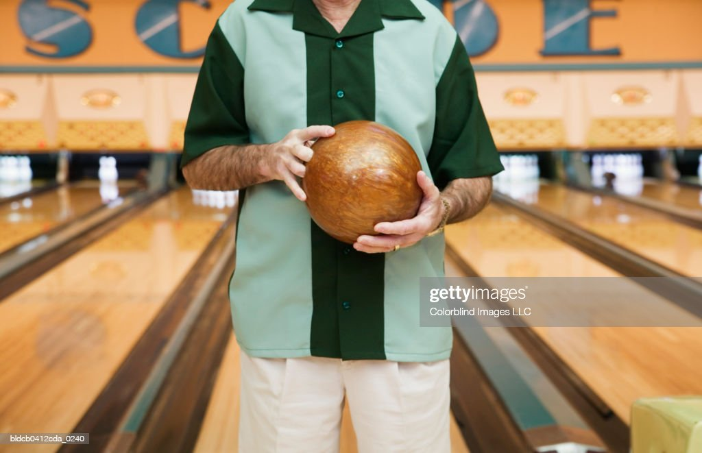Mid section view of a mid adult man holding a bowling ball in a bowling alley : Foto de stock