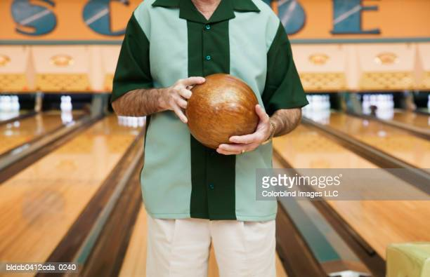 Mid section view of a mid adult man holding a bowling ball in a bowling alley