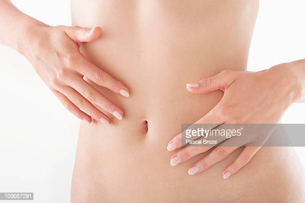 Mid section view of a naked woman touching her abdomen