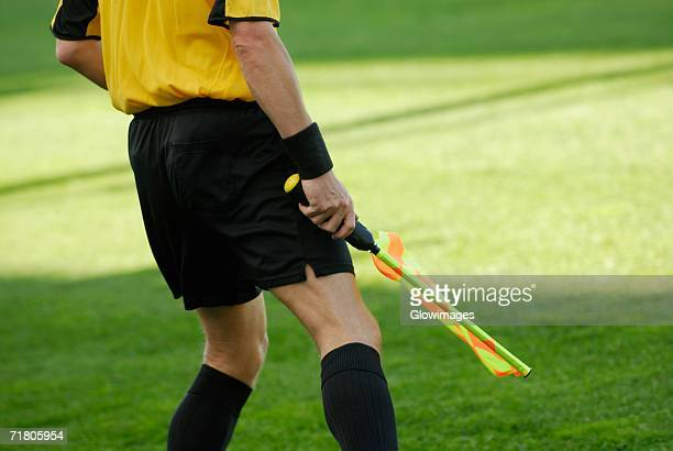 mid section view of a referee holding a flag - referee stock photos and pictures