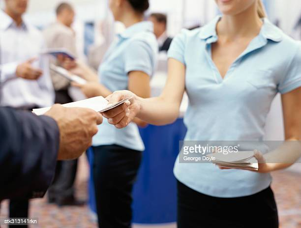 mid section view of a sales executive giving brochure to a businessman