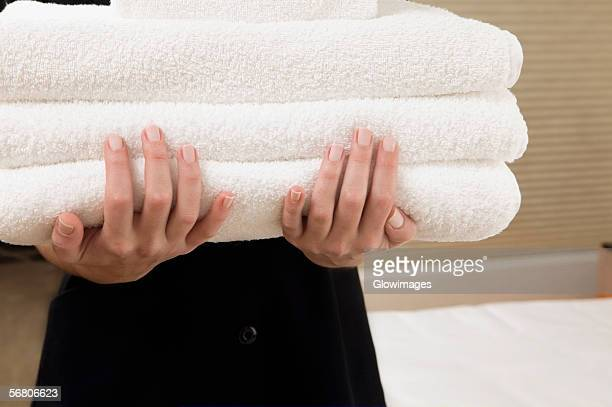 Mid section view of a waitress holding a stack of towels