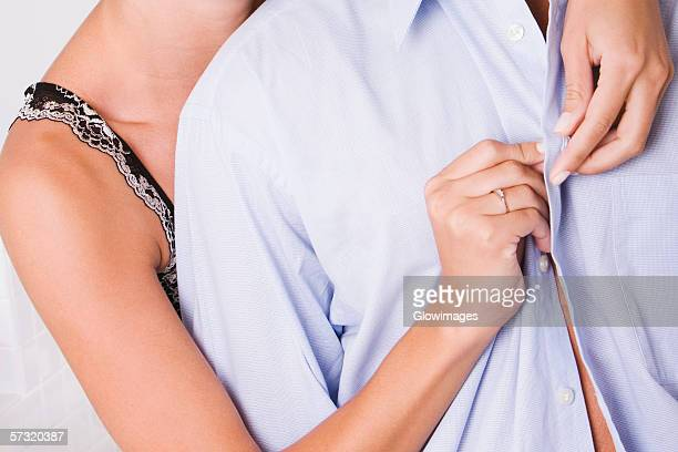 Mid section view of a woman buttoning a man's shirt from behind