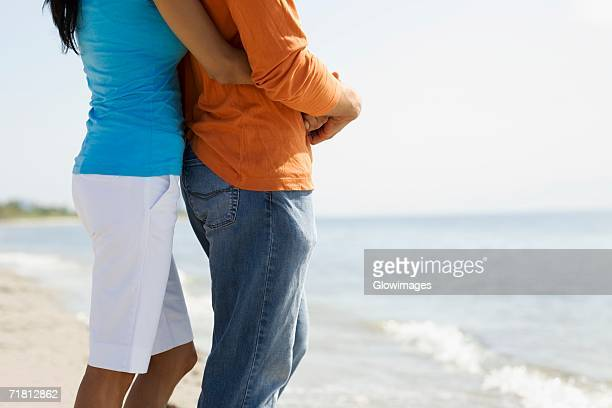 mid section view of a woman embracing a man from behind on the beach - pedal pushers stock pictures, royalty-free photos & images