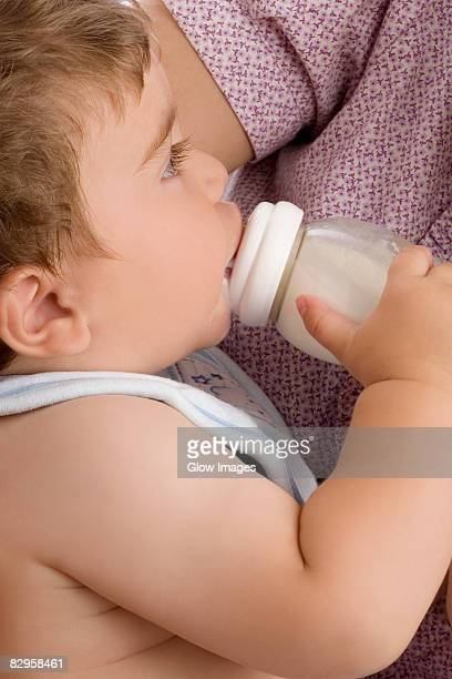 Mid section view of a woman feeding her son with a baby bottle