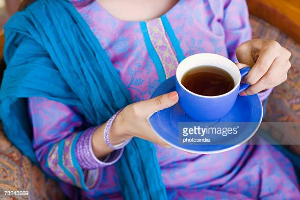 mid section view of a woman holding a cup of tea - salwar kameez stock pictures, royalty-free photos & images