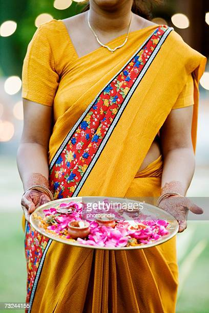 Mid section view of a woman holding oil lamps and Rose petals in a plate
