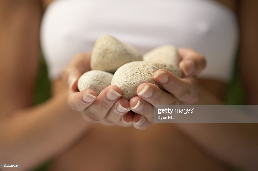Mid Section View of a Woman Holding Pebbles in Her Cupped Hands : Stock Photo