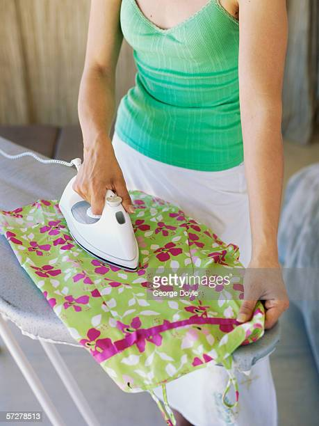 Mid section view of a woman ironing
