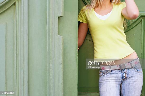 Mid section view of a woman leaning against a wall