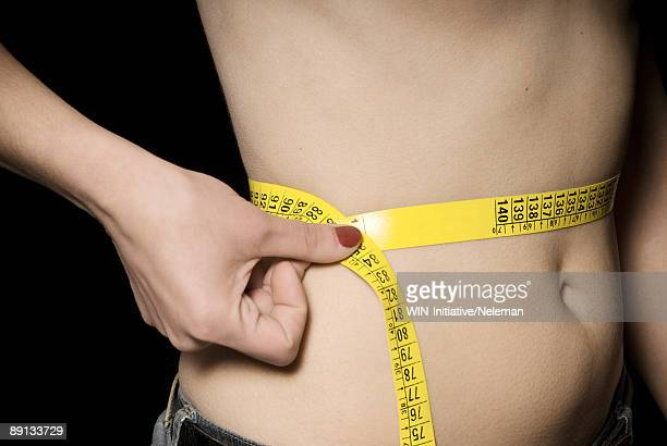 Mid section view of a woman measuring her waistline