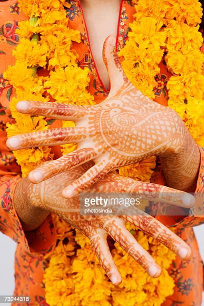 Mid section view of a woman showing her henna tattooed hands