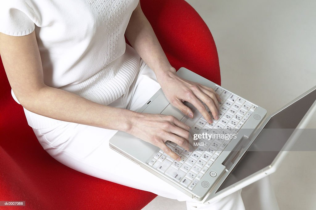 Mid Section View of a Woman Sitting in a Chair and Typing on a Laptop : Stock Photo