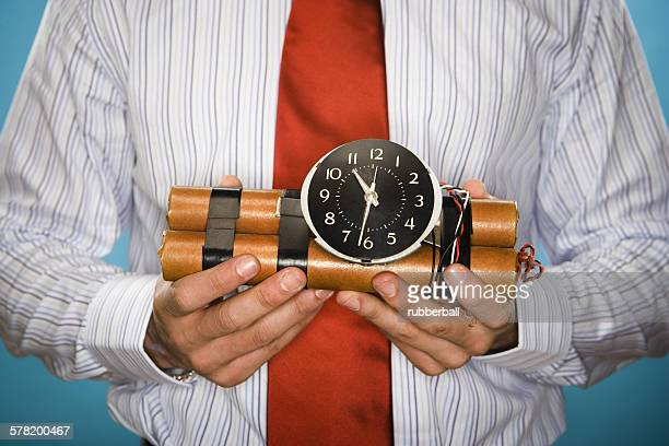 mid section view of a young man holding a time bomb - time bomb stock photos and pictures