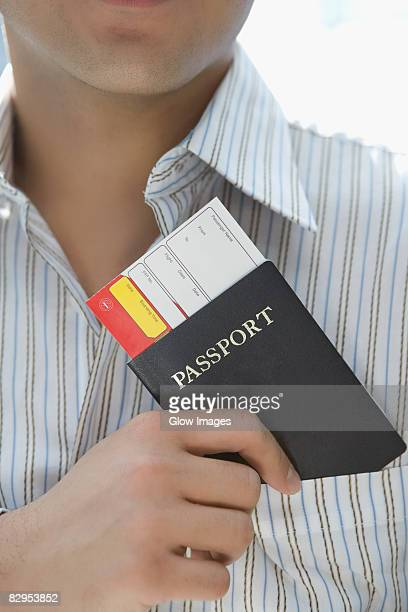 Mid section view of a young man putting a passport with an airplane ticket in his shirt's pocket
