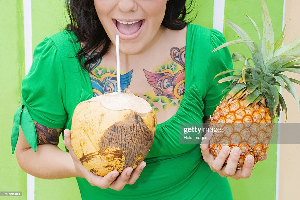 Mid section view of a young woman holding a pineapple and drinking coconut milk with a drinking straw : Foto de stock