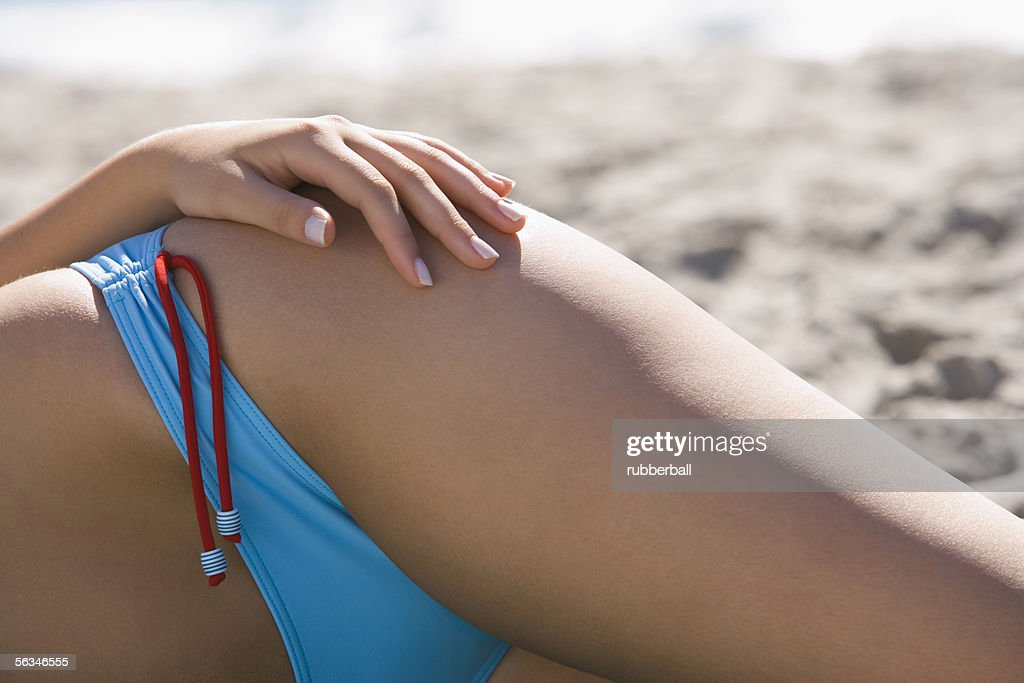 Mid section view of a young woman sunbathing on the beach : Stock Photo