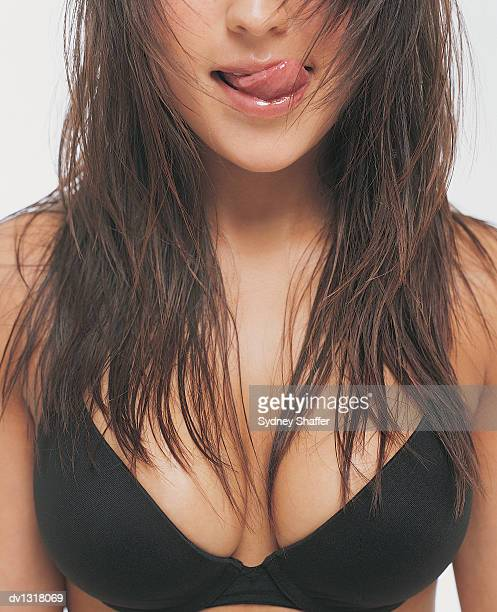 Mid Section View of a Young Woman Wearing a Bra and Licking Her Lips