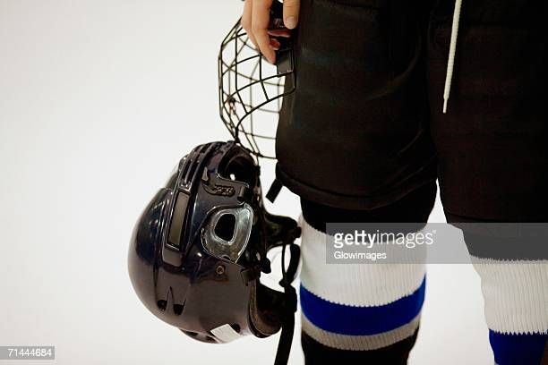 mid section view of an ice hockey player holding a helmet - ice hockey uniform stock pictures, royalty-free photos & images