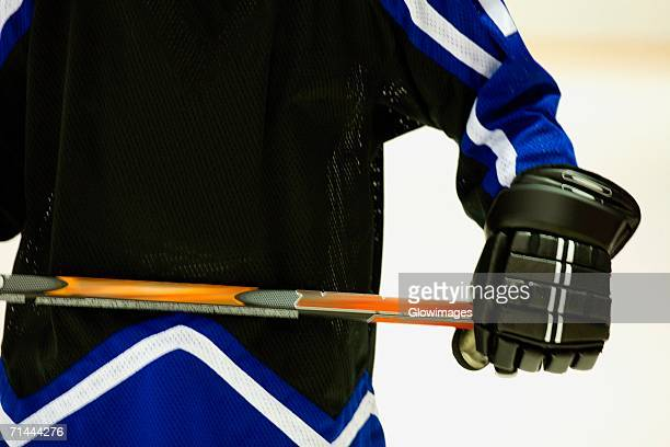Mid section view of an ice hockey player holding an ice hockey stick