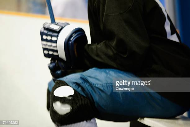 mid section view of an ice hockey player holding an ice hockey stick - ice hockey glove stock pictures, royalty-free photos & images