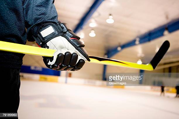 mid section view of an ice hockey player holding an ice hockey stick - ice hockey uniform stock pictures, royalty-free photos & images