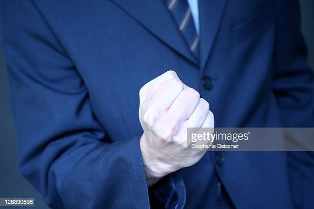 Mid section view of businessman making fist
