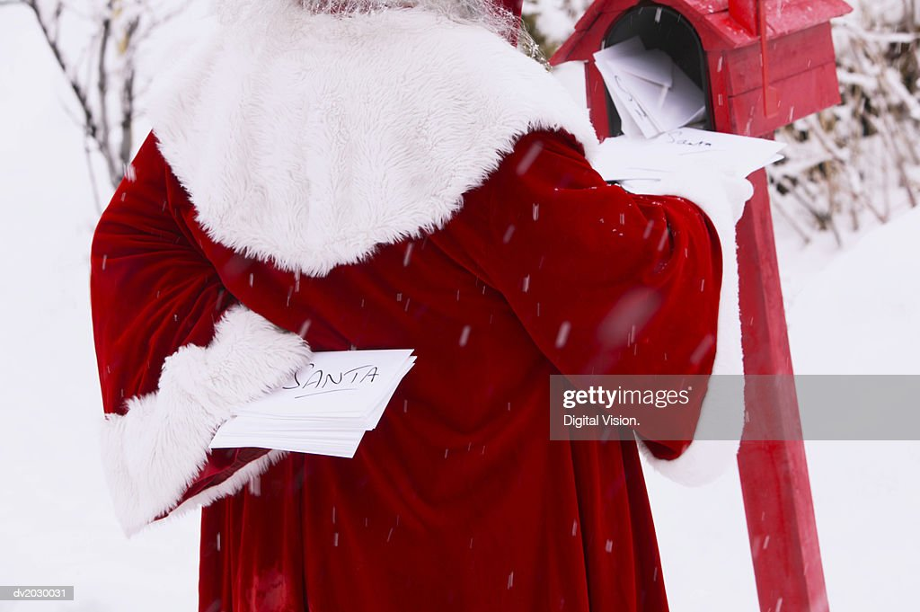 Mid Section View of Father Christmas Inserting Christmas Cards Into a Mail Box : Stock Photo