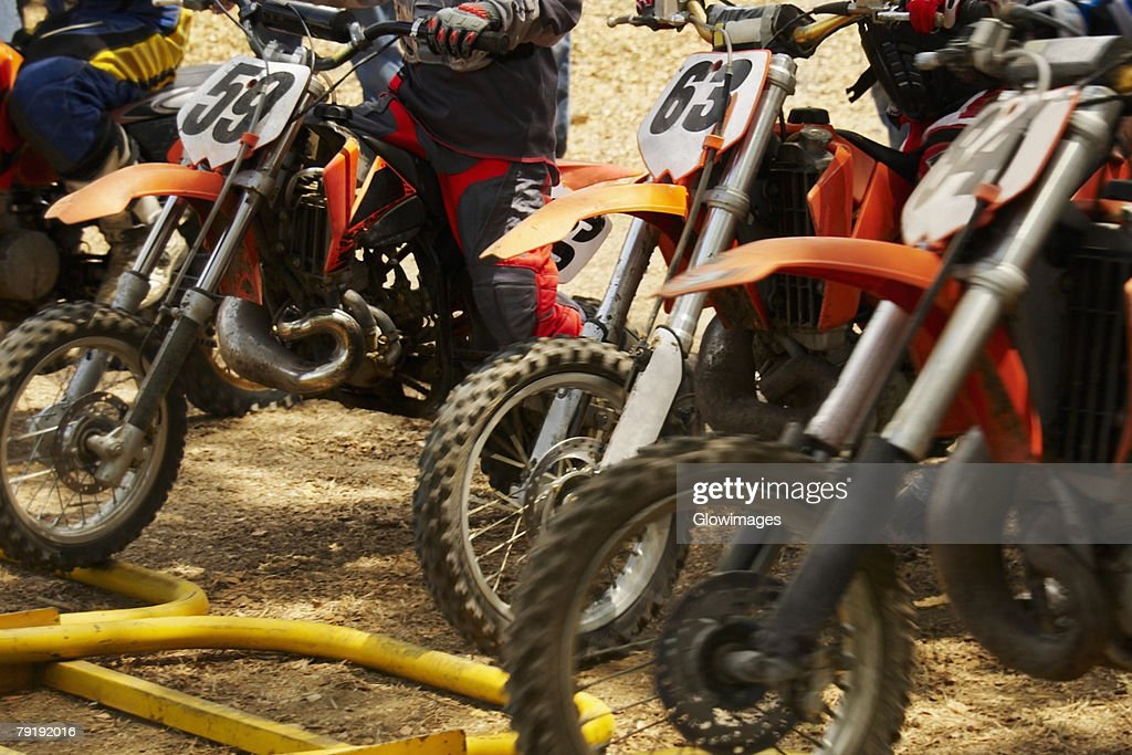 Mid section view of motocross riders on their motorcycles : Stock Photo