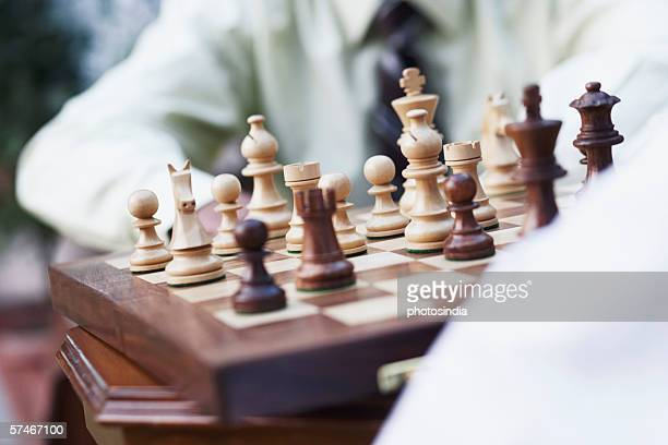 Mid section view of two businessmen playing chess